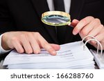 Small photo of Businessman Looking At Document Through Magnifying Glass