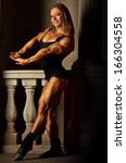 Young woman bodybuilder on ancient background. - stock photo