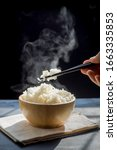 Small photo of The man hand of using black chopsticks holding hot jasmine rice with smoke and steam in black bowl over dark background.hot food concept