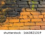 Small photo of Color splotch orange yellow black painted brick wall