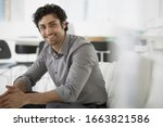 Small photo of An office in the city. Business. A man seated with his hands clasped in a relaxed pose. Smiling and leaning forwards.