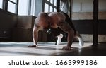 Small photo of Young strong muscular shirtless Caucasian male athlete doing burpee exercises during functional workout in large gym.