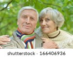 happy senior couple walking in... | Shutterstock . vector #166406936