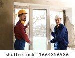 Workers in uniform installing plastic window indoors - stock photo