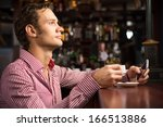 man with a cup of coffee at the ... | Shutterstock . vector #166513886