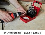 sets the Drill bit in the drill,hands take the drill bit and install in the electric drill - stock photo