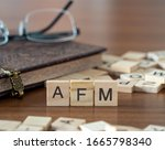 Small photo of the acronym afm for Acute Flaccid Myelitis concept represented by wooden letter tiles on a wooden table with glasses and a book