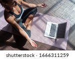Small photo of Top view young sporty slim woman coach internet video online training hatha yoga instructor modern laptop screen meditate Sukhasana posture relax breathe easy seat pose gym healthy lifestyle concept.