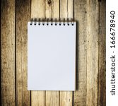 black notebook on a wood... | Shutterstock . vector #166678940