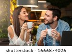 Small photo of Dating. Young couple tasting coffee drinks enjoying flirt and conversation during weekend date sitting in cozy cafe