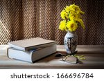 Still life, books on the wooden table near vase of yellow flower and glasses - stock photo