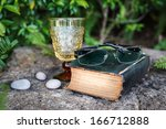 Glasses place above dirty old book near vintage glass on the rock - stock photo