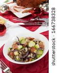 Brussels sprouts with bacon and mushrooms side dish. Carved roasted spiced ham appetizers with Christmas ornaments.  - stock photo