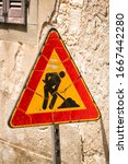 Small photo of Triangular safety sign warning their are workman ahead on a street in the Italian village of Barga