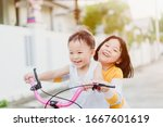 Small photo of Big sister try to ride bicycle with her brother ride in front on the road in summer.Asian sibling kid playing and ride bike together.Family with children at home.Love, trust and sibling fun together.