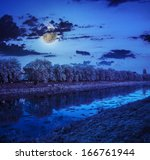 bank of the river with trees covered with rime on in moon light a winter night - stock photo