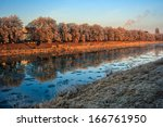 bank of the river with trees covered with rime on a winter morning - stock photo