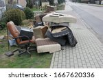 Small photo of Old damaged furniture extruded on a pile of unnecessary things on the grass and pavement in the spring
