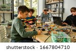 Small photo of Young technicians building robots and vehicles, using soldering iron to join chips and wires, programming toys at stem robotics class. Inventions and creativity for kids