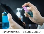 Small photo of Hand of woman is spraying alcohol,disinfectant spray on mobile phone,prevent infection of Covid-19 virus,contamination of germs or bacteria,wipe or cleaning phone to eliminate,outbreak of Coronavirus
