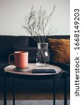 Small photo of Modern interior details. Little round table with ceramic red color cup of delicious earl gray tea. Resting after work day at home, offline. Selective focus. Vertical photo