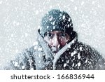 Small photo of Wintery scene of shivering man in snowstorm or ice storm