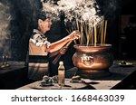 Man Placing Smoking Incense...