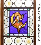 Small photo of Milwaukee, Wisconsin / USA - Jan 11, 2020: Stained glass within the miller guest house with different depictions of people with beer. Miller girl sitting on the moon