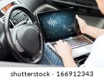 transportation and vehicle concept - man using laptop computer in car - stock photo