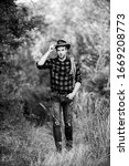 Small photo of Hes a cowboy aint he. man checkered shirt on ranch. cowboy with lasso rope. Western. Vintage style man. Wild West retro cowboy. western cowboy portrait. wild west rodeo. man in hat outdoor.