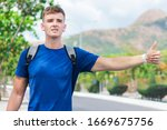 Small photo of Handsome guy, young man traveler trying to stop, catch taxi car, cab. Boy standing near road with backpack, wireless earphones holding out his hand with thumb up, hitchhiking sign. Hitchhiker, summer