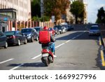 Delivery service from cafes and restaurants, delivery boy on scooter with red backpack driving fast. Courier delivering food on motorbike. Quick deliver food to customers - stock photo