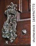 Old Metal Knocker At A Wood Door