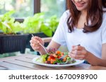 Small photo of The smiling woman enjoys eating a salmon salad. To lose weight and diet, eat foods that are beneficial to the body. Weight loss concept.