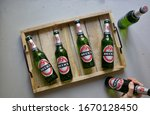 Small photo of Berlin, Germany 10/3/2020 Cold fresh Beck's German beer ingrain bottles on rustic wooden tray.