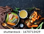 Small photo of fish broth or soup of salmon, onion, carrot, celery, herbs and spices in a stockpot and in a white bowl on a concrete table with ingredients, free space, horizontal view from above, flat lay, close-up