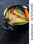 Small photo of slow-cooked fish broth or soup of salmon, onion, carrot, celery, herbs and spices in a stockpot on a concrete table, vertical view from above