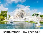 Small photo of The white temple (Wat Rong Khun) in Chiang Rai city, Thailand. Beautiful buddhist ancient building with bridge above damned souls of sinners, path to the heaven. Famous tourist destination. Blue sky.