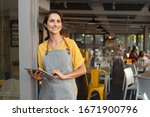 Small photo of Portrait of a happy waitress standing at restaurant entrance holding digital tablet. Happy mature woman owner in grey apron standing at coffee shop entrance leaning while looking away with copy space.