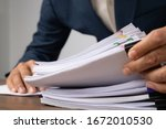 Small photo of Man hand pick up Stack overload document report paper with colorful paperclip, business and paperless concept.