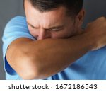 Small photo of Close-up. Caucasian male coughs in his elbow. Correct sneezing. Concept of stop spread of the virus.