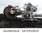Small photo of Bucket-wheel excavator during excavation at the coal surface mine. Huge excavator on open pit mine.