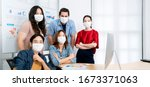 Small photo of asian small business startup multiracial brainstorm meeting with laptop and chart paper everyone mask for covid19 protection corona flu prevent healty ideas concept office background