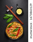 Small photo of Chicken Lo Mein in black bowl at dark slate background. Lo Mein is Chinese cuisine dish with chicken meat, egg noodles, vegetables and sauces. Chinese Food. Stir Fried Noodles. Top view