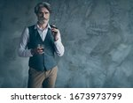 Small photo of Portrait of brutal harsh masculine old dandy man hold cigar glass whiskey have relax work enterprise day wear shirt brown vest trousers isolated over grey concrete wall background