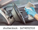 Cleansing car interior and spraying with disinfection liquid. Hands in rubber protective glove disinfecting vihicle inside for protection from virus disease - stock photo