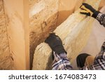 Synthetic Mineral Fibers Wall Insulation Job. Construction Worker Insulating House Walls with Thermal Material.  - stock photo