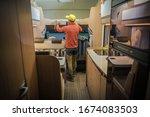 Men Preparing RV For Summer Season Looking on Bunk Bed. Modern Class C Motorhome Interior. Recreational Vehicle. - stock photo