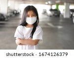 Small photo of Asian child positive or kid girl smiling wear N95 cloth face mask for close mouth and sick on nose with cold cough and protect PM2.5 dust or influenza virus and bacteria from smoke and crossed arms