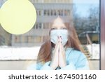 Small photo of portrait of a red-haired girl behind glass in a protective face mask as a concept of quarantine and isolation due to the covid-19 coronavirus, border closure and social disunity, empty frame for text